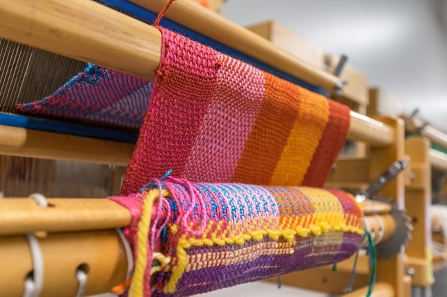 A photograph depicts colorful fabrics stretched across a weaving loom