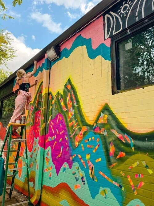 A figure stands on a ladder to paint a colorful mural on the side of a building