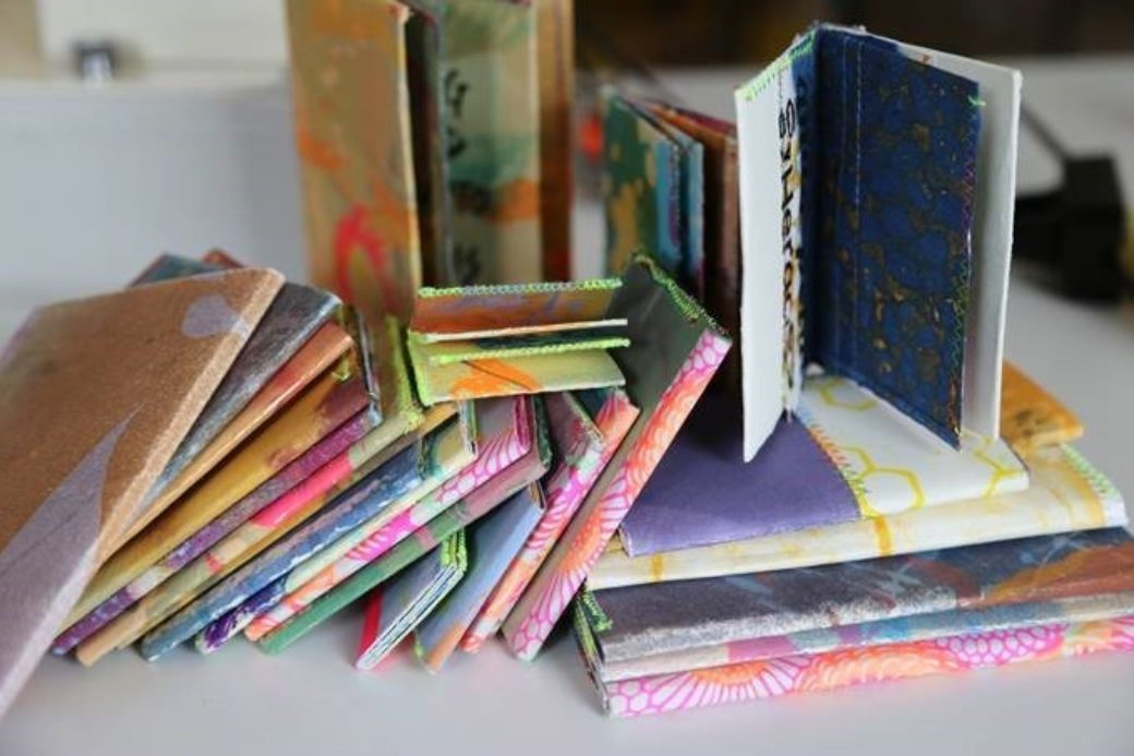A collection of colorful, hand-bound art books scattered on a table