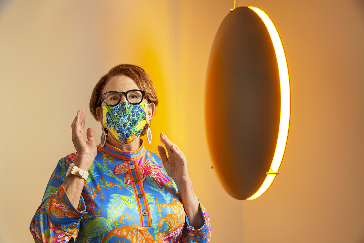 A figure in a vibrant face covering poses next to a light-emitting sculpture in the shape of a black disc