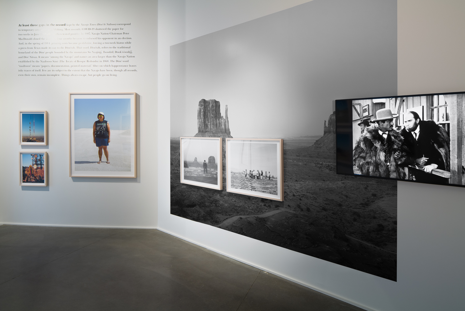 A wall in an art gallery depicts various photographs of Western landscapes, both framed and emblazoned on the wall itself, along with a video screen displaying an image of a black-and-white film