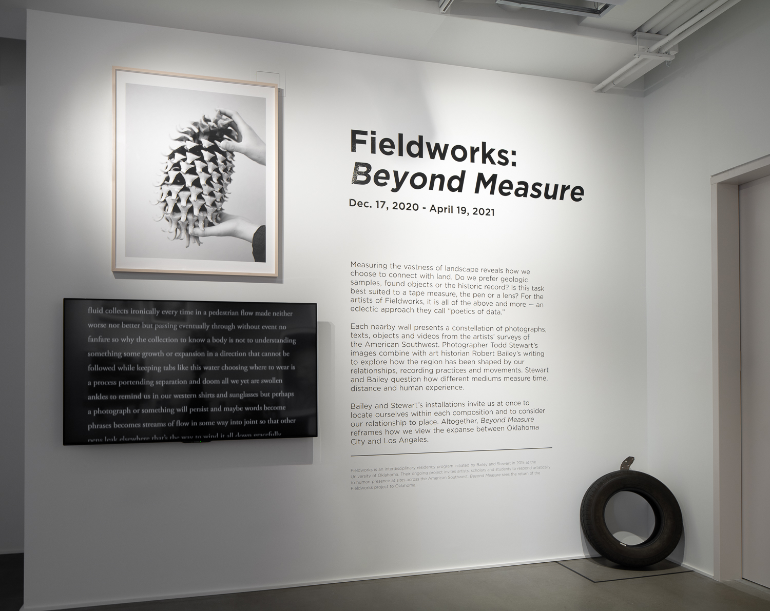 The title wall of an exhibition in an art gallery, featuring text, video, a framed black-and-white photo and a car tire propped in the corner