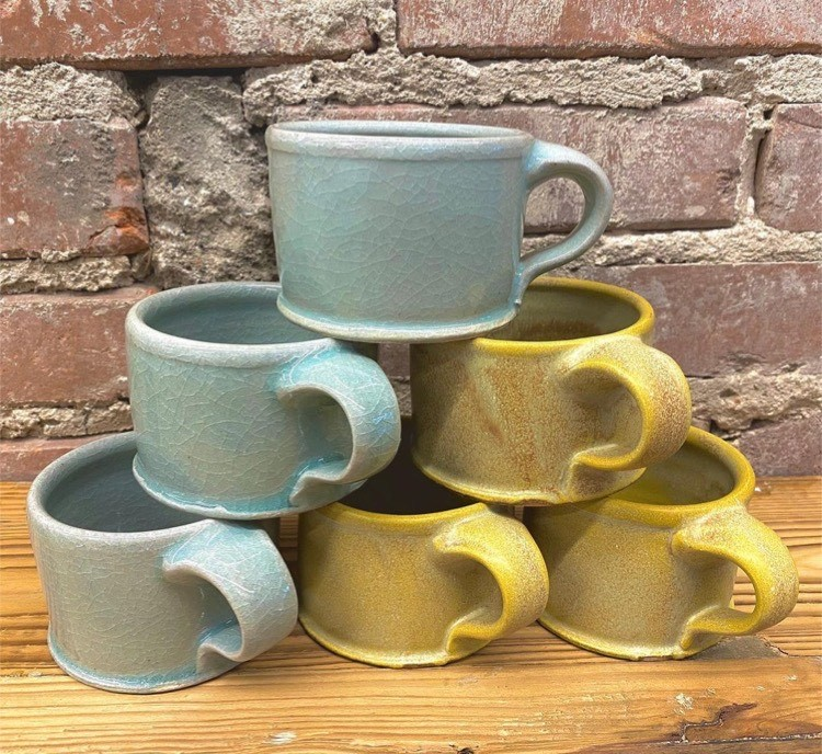 Six handmade ceramic mugs stacked in a triangle: three blue and three yellow