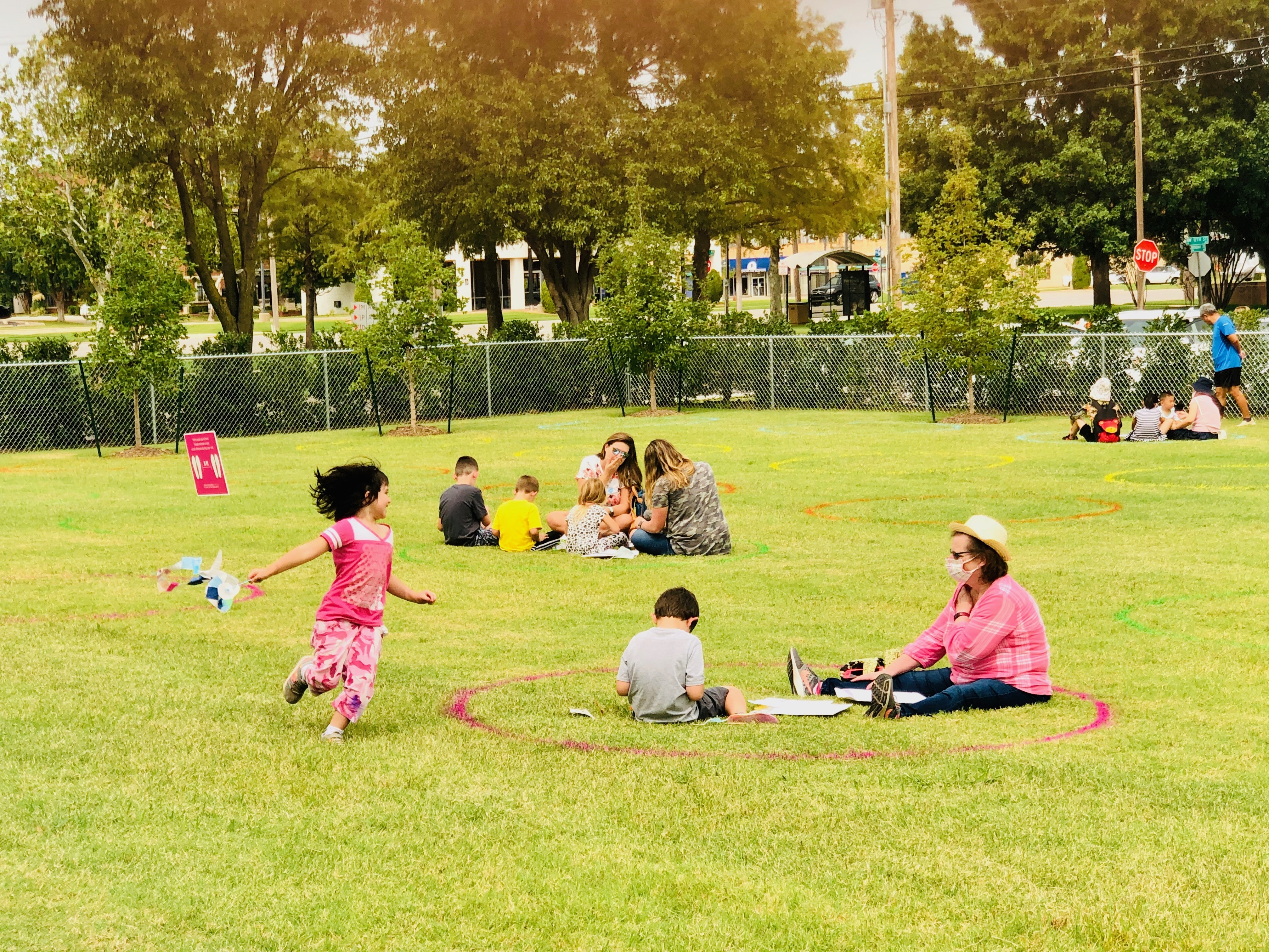 Families enjoy outdoor activities, sitting in socially distanced circles marked on a green lawn