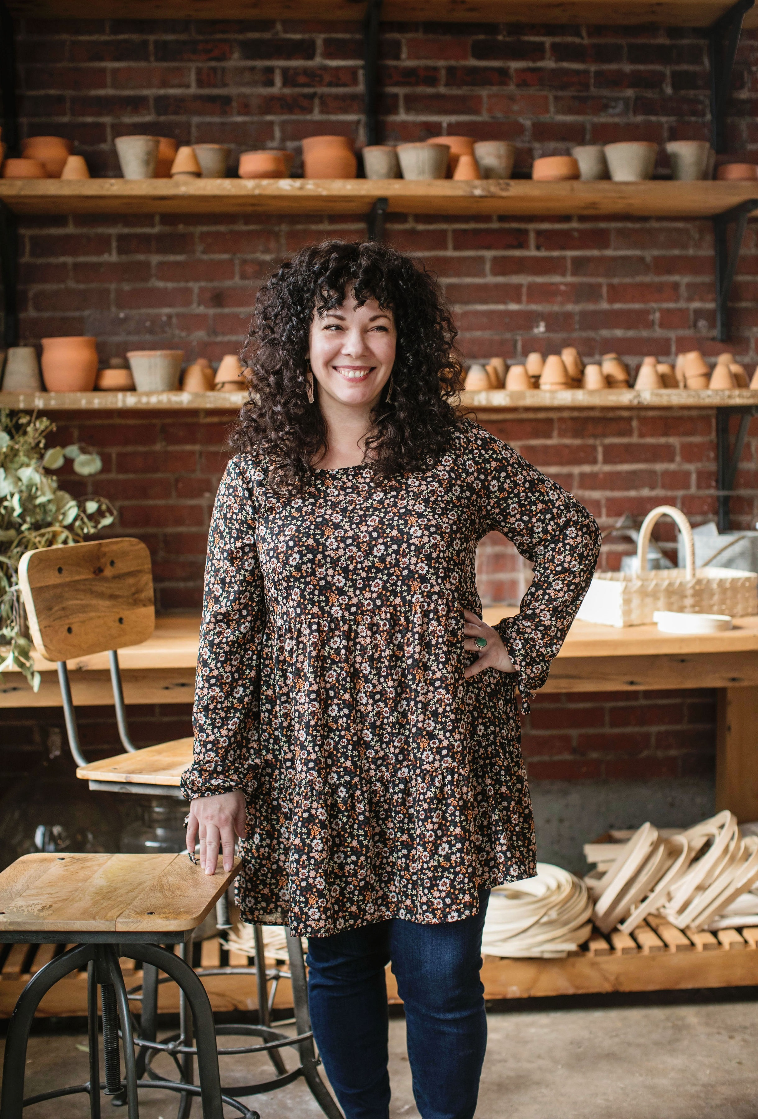 A figure with dark curly hair stands and smiles in front of shelves filled with ceramic artwork