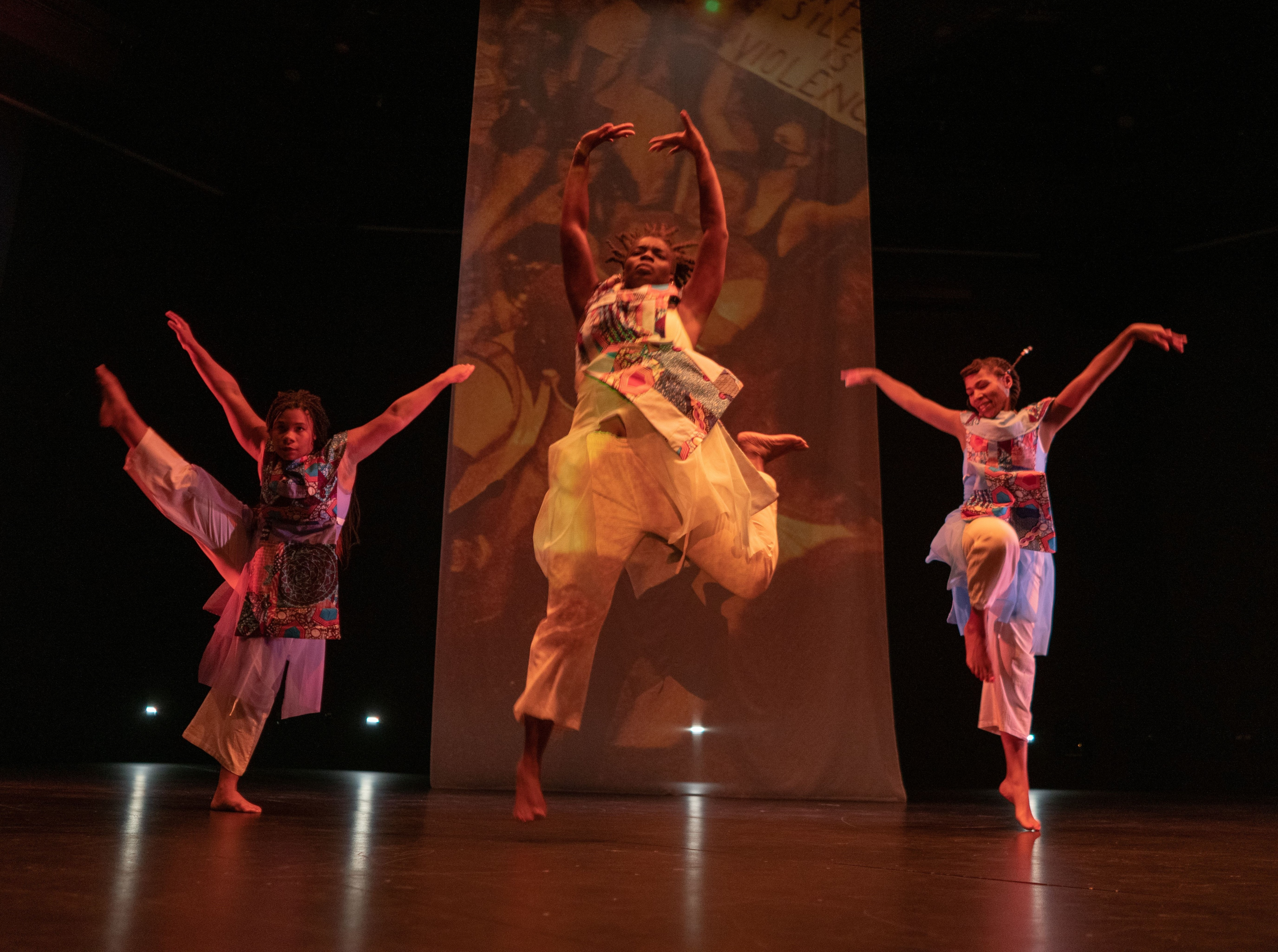 Three dancers in flowing costumes perform in front of a scrim in a dark theater