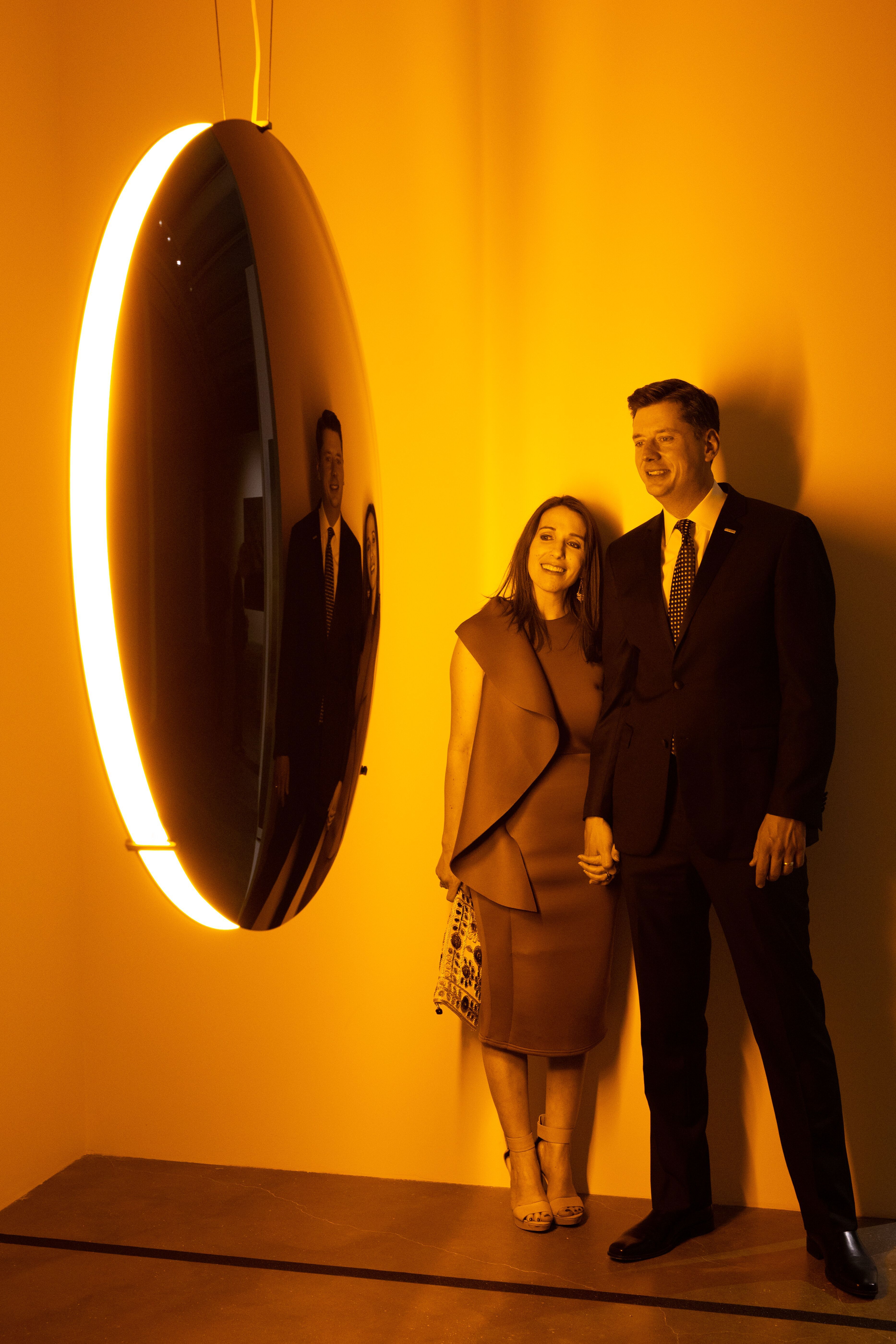 A young couple holds hands and views a suspended glass disc encompassed in a yellow glowing light