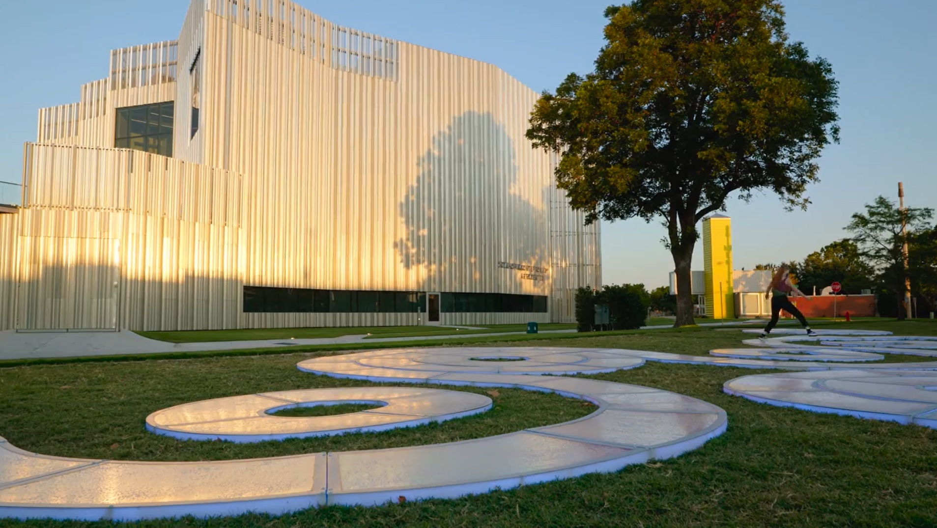 A daytime photo depicts the reflective surface of a winding sculptural path in front of a contemporary building