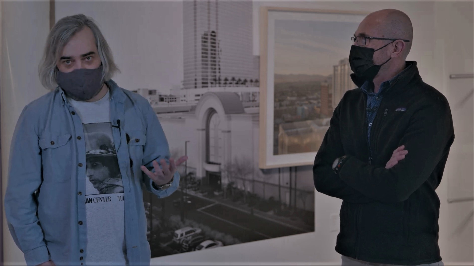 Two masked people talking in front of a wall of photographs in an art gallery