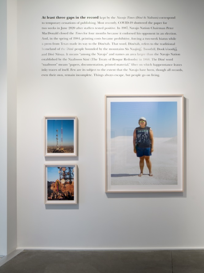 A lengthy written narrative on a white wall contextualizes three photographs depicting people and machinery in the American West