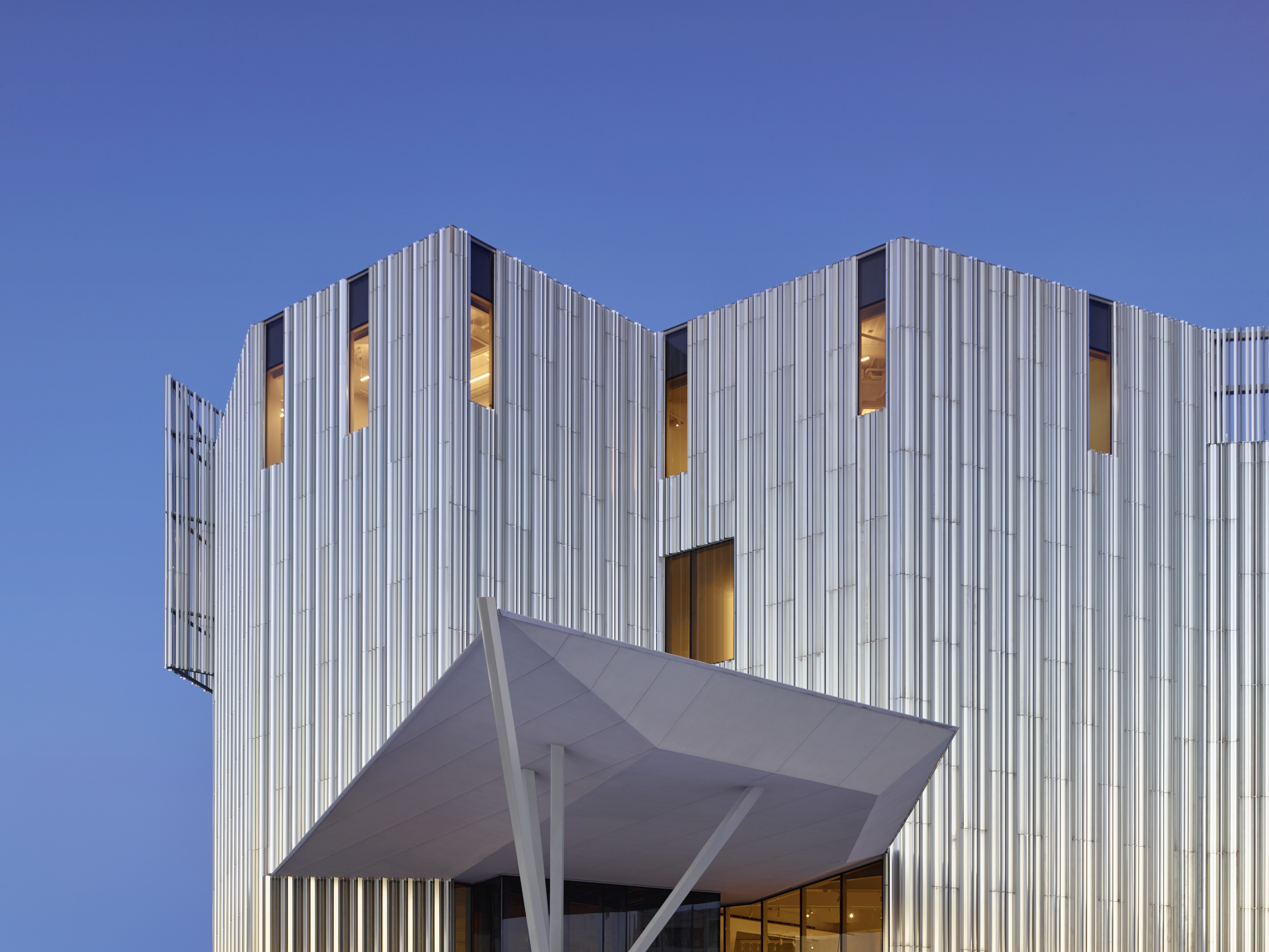 A detail photo of the top portion of a building, featuring sharp angles and covered in aluminum fins, against an early evening sky