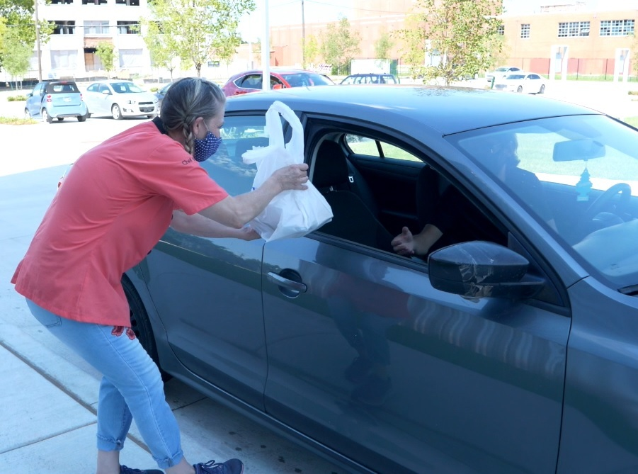 A figure hands a plastic bag to a driver through the passenger side window of their car