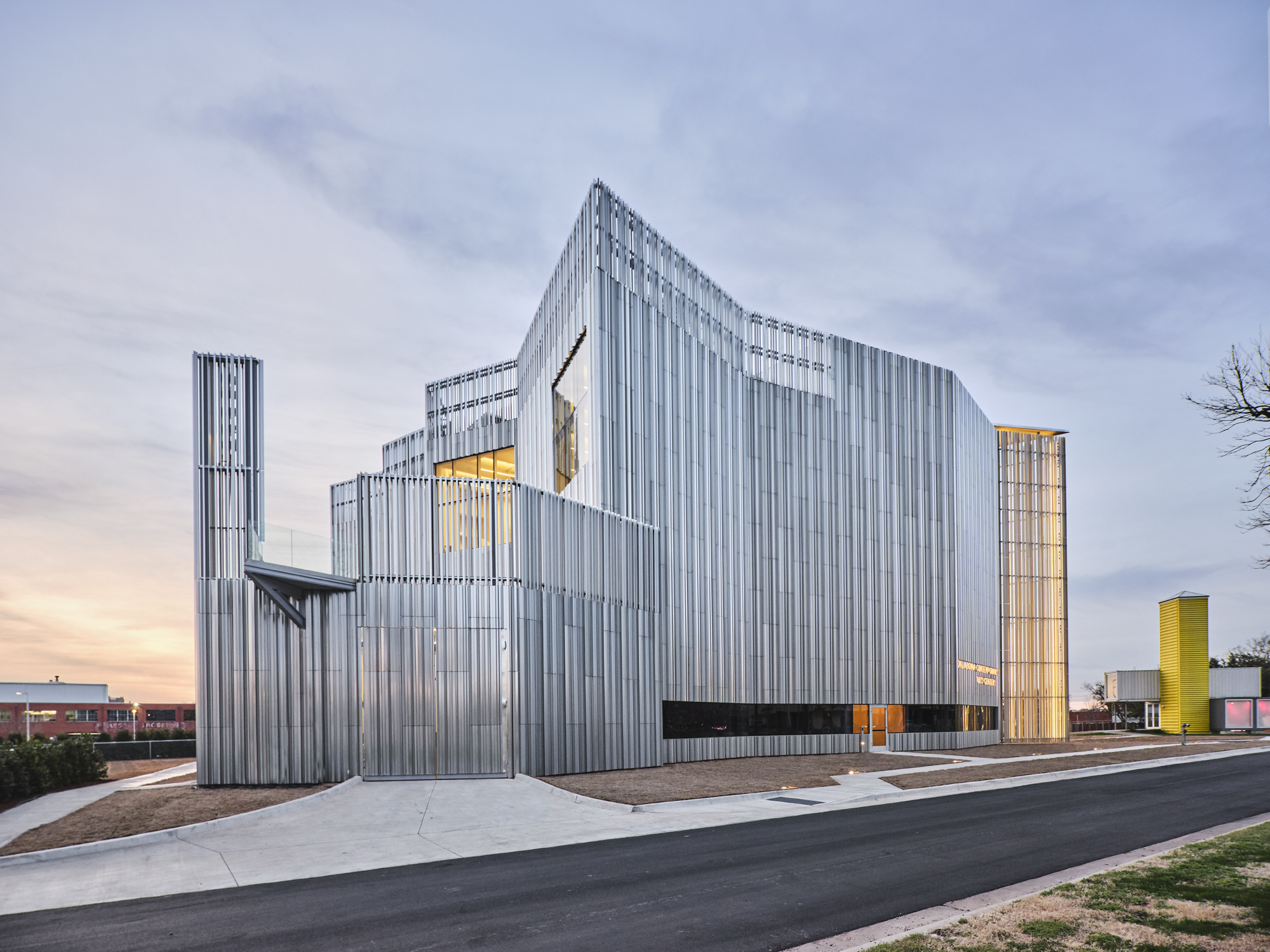A dramatic metal building reflects the sunset