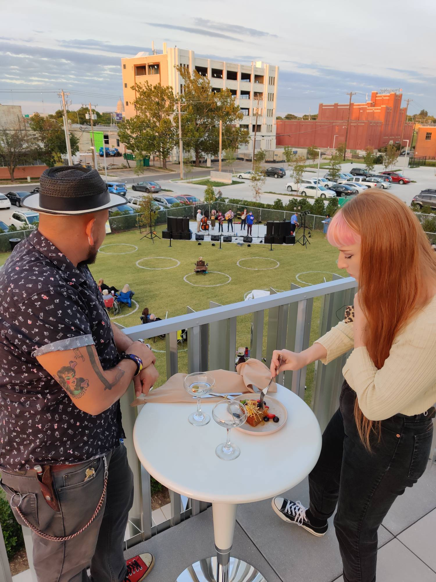 Two people eat and drink outdoors, overlooking a concert on a green lawn