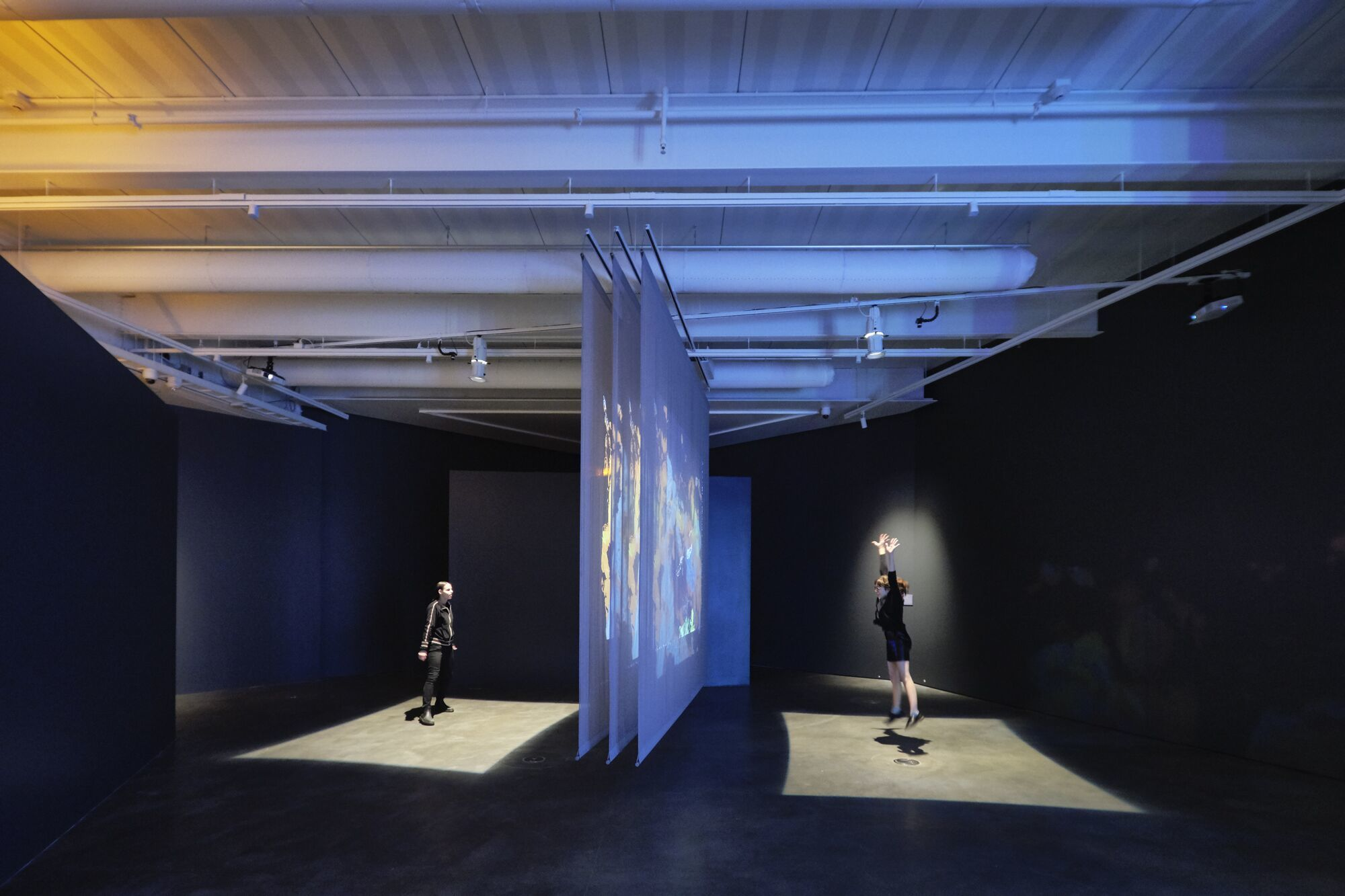Three fabric scrims hang from a gallery ceiling, while abstract images project on them as two adults interact with the installation