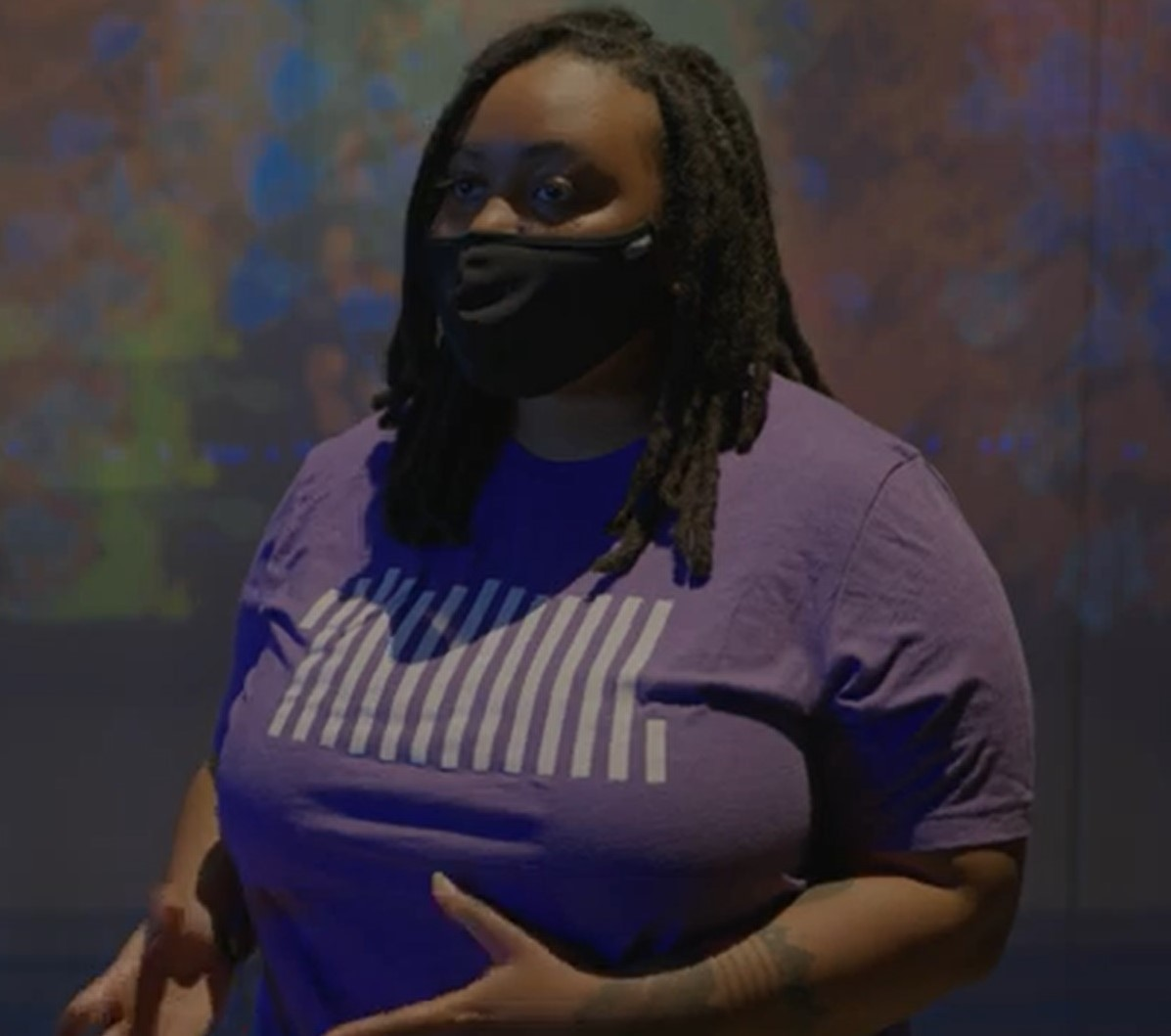 A person wearing a black mask and purple T-shirt speaks in front of an abstract art installation