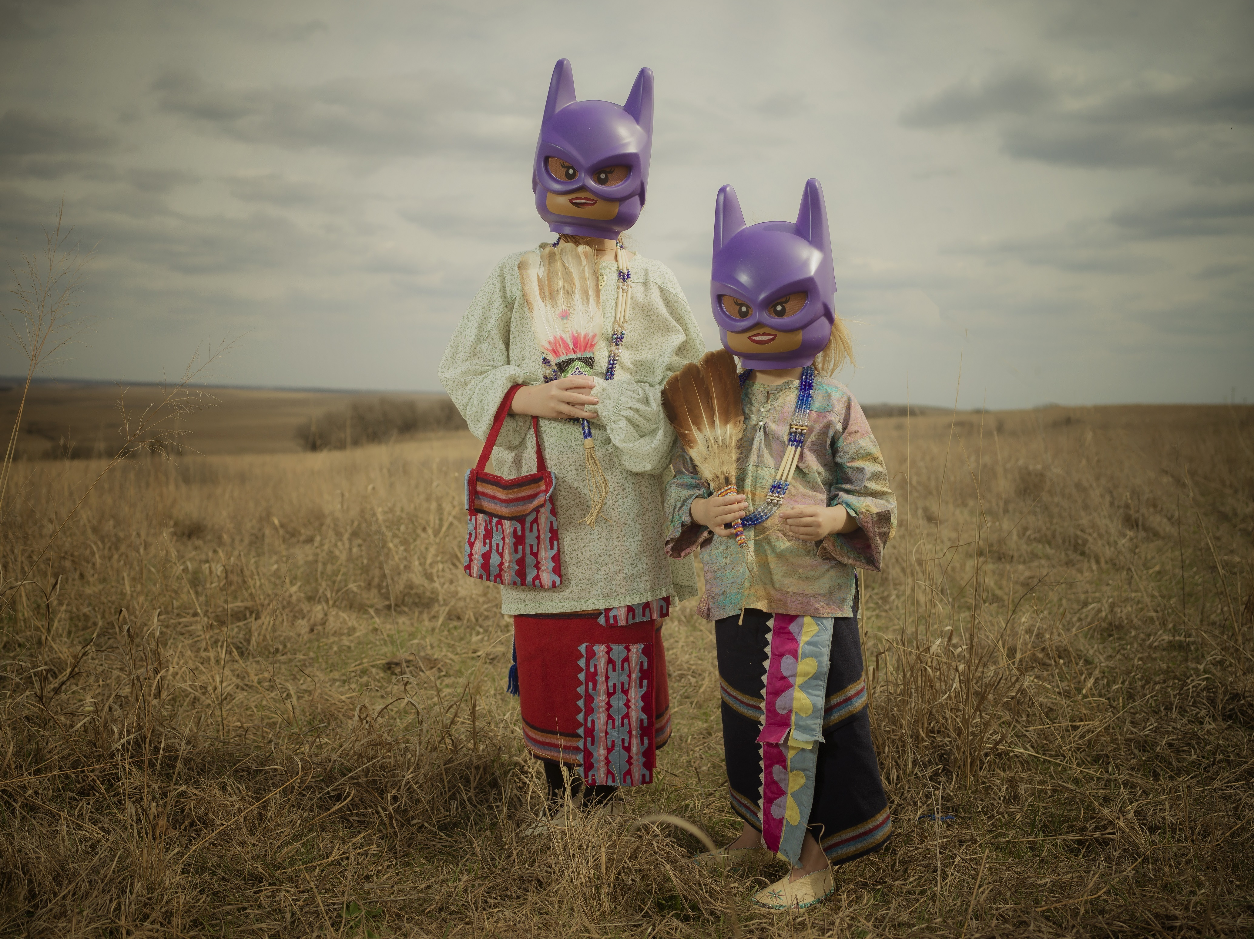 An artistic photograph depicts two young children wearing Native regalia and purple Bat Girl masks on an open prairie