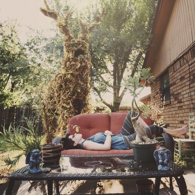 A surreal photograph depicts a figure lying on a couch outdoors, with a mystical tree-like creature in the background