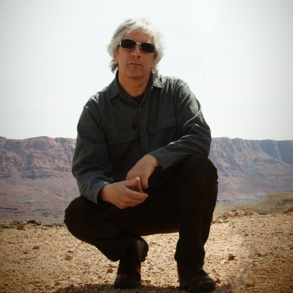 A figure in sunglasses crouches in the middle of a desert