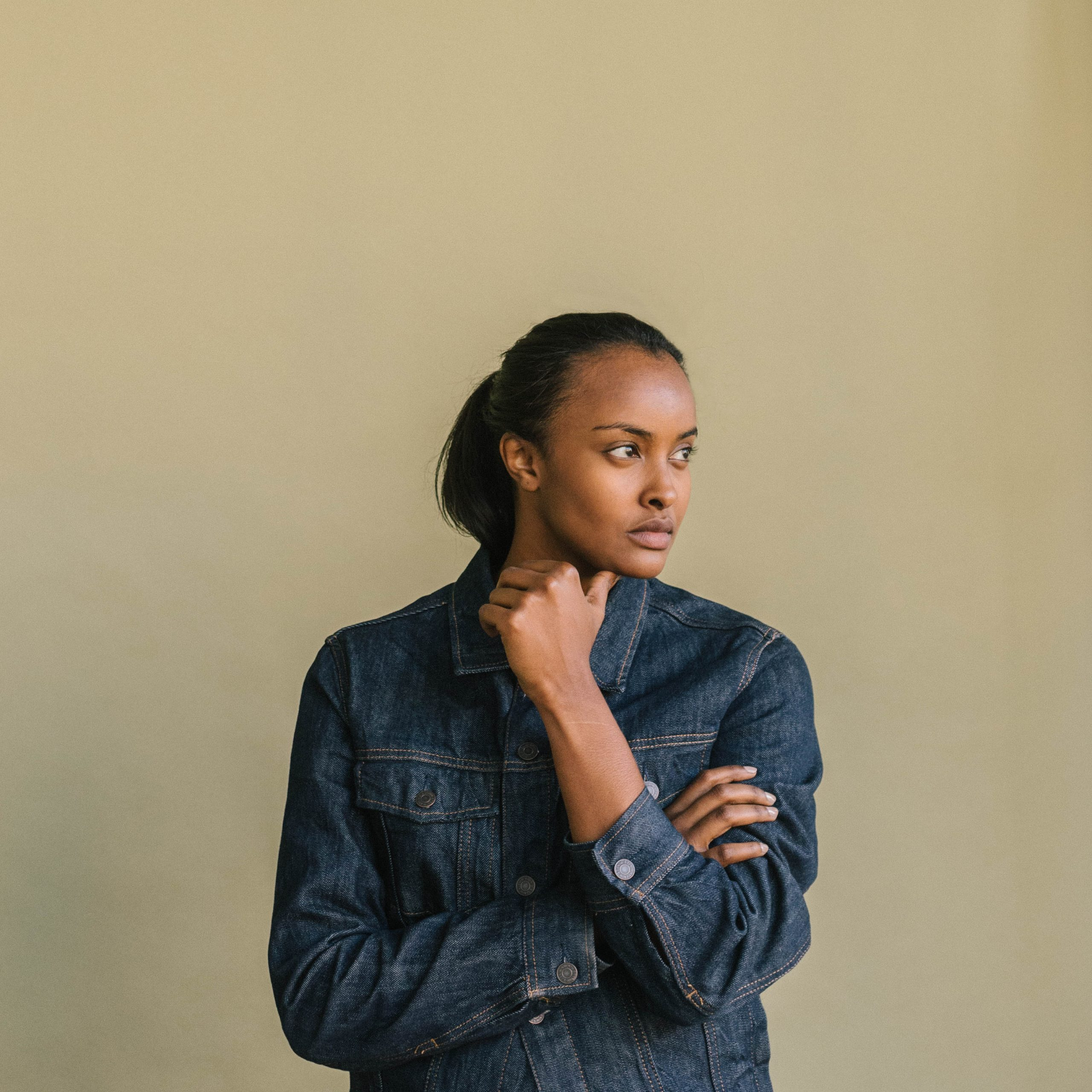 A figure in a denim shirt looks away from the camera