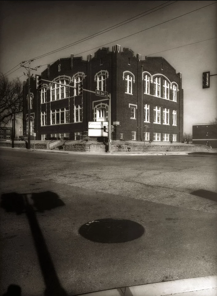 A black and white photo with a brick building sitting on the corner of a street in the background and the street itself, with a manhole cover and the shadow of a street sign, in the foreground