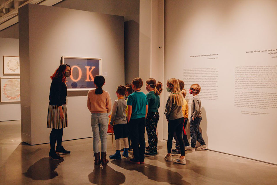 """A person shows a group of children a piece of art with an """"O"""" and a """"K"""" on it."""