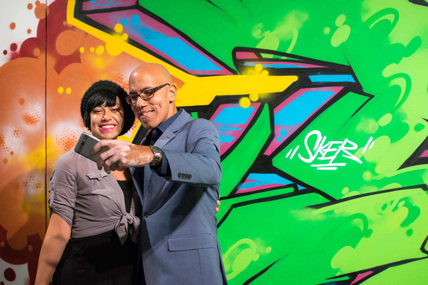 Two people take a selfie in front of a brightly colored mural